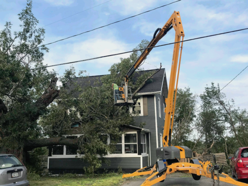 Picture of our climber in a lift bucket trimming a tree back from a house in Iowa City, IA